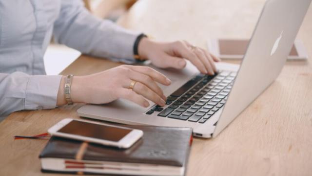 ノートパソコンのキーボードをたたく手指
